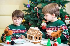 Two sweet boys, brothers, making gingerbread cookies house, decorating at home in front of the Christmas tree, child playing and. Enjoying, Christmas concept royalty free stock photography