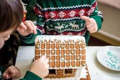 Two sweet boys, brothers, making gingerbread cookies house, decorating at home in front of the Christmas tree, child playing and. Enjoying, Christmas concept stock images