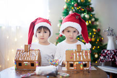 Two sweet boys, brothers, making gingerbread cookies house Stock Photography