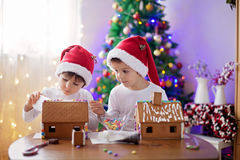 Two sweet boys, brothers, making gingerbread cookies house. Decorating at home in front of the Christmas tree, child playing and enjoying, Christmas concept Stock Photos
