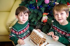 Two sweet boys, brothers, making gingerbread cookies house, decorating at home in front of the Christmas tree, child playing and. Enjoying, Christmas concept royalty free stock image