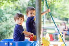 Two sweet boys, brothers, playing in a boat on the playground. Summertime outdoors stock photos