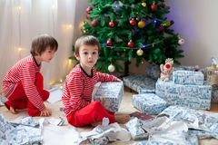 Two sweet boys, opening presents on Christmas day. Two sweet children, boy brothers, opening presents on Christmas day, still in pajamas. Kids happiness Royalty Free Stock Image