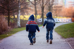 Two sweet boys running away on a footpath in the park on a sunny. Winter day, outdoors activity royalty free stock images