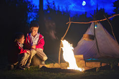 Two sweet boys, sitting around the campfire after sunset. Listening scary stories royalty free stock image