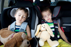 Two sweet boys, sleeping in the car with teddy bears Royalty Free Stock Images
