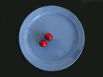 Two sweet cherries. On a blue plate stock images