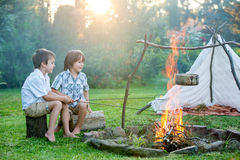 Two sweet children, boy brothers, camping outside summertime on Stock Photos