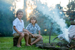Two sweet children, boy brothers, camping outside summertime on Stock Photo