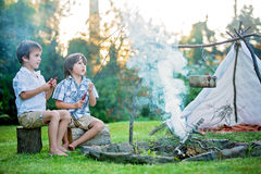 Two sweet children, boy brothers, camping outside summertime on Stock Images