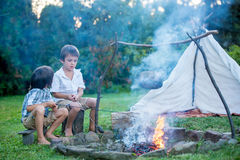 Two sweet children, boy brothers, camping outside summertime on Royalty Free Stock Photos