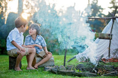 Two sweet children, boy brothers, camping outside summertime on Royalty Free Stock Photography