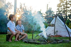 Two sweet children, boy brothers, camping outside summertime on Royalty Free Stock Photo