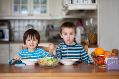 Two sweet children, boy brothers, having for lunch spaghetti at Stock Image