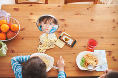 Two sweet children, boy brothers, having for lunch spaghetti at Stock Photography