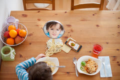 Two sweet children, boy brothers, having for lunch spaghetti at Royalty Free Stock Image