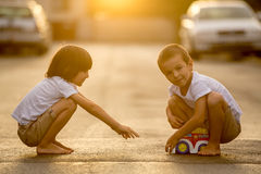Two sweet children, boy brothers, playing with car toys on the s Stock Photos