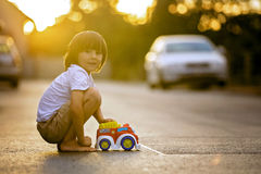 Two sweet children, boy brothers, playing with car toys on the s Royalty Free Stock Photo