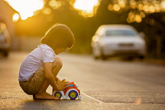 Two sweet children, boy brothers, playing with car toys on the s Royalty Free Stock Photography