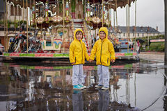Two sweet children, boy brothers, watching carousel in the rain, Stock Photo