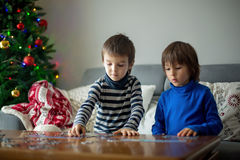 Two sweet children, collect puzzles at home on Christmas. Two sweet children, collect puzzles at home sitting on a couch on Christmasm christmas decoration Royalty Free Stock Photos