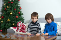 Two sweet children, collect puzzles at home on Christmas. Two sweet children, collect puzzles at home sitting on a couch on Christmasm christmas decoration Stock Photos