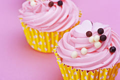 Two sweet cupcake with chocolate balls  on a pink backgr Royalty Free Stock Photography
