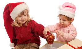 Two sweet girls in Santa hats, isolated Stock Photos