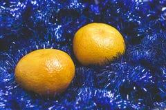 Two sweet, juicy mandarin lie on blue Christmas tinsel. Two sweet, juicy mandarin lie on blue Christmas tinsel stock photo