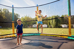 Two sweet kids, brothers, jumping on a trampoline, summertime, h. Aving fun. Active children stock image