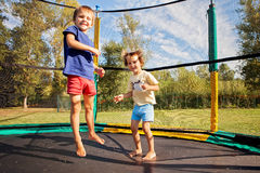 Two sweet kids, brothers, jumping on a trampoline, summertime, h. Aving fun. Active children royalty free stock images