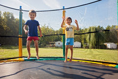 Two sweet kids, brothers, jumping on a trampoline, summertime, h. Aving fun. Active children royalty free stock photography