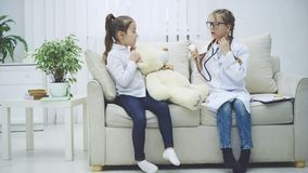Two sweet kids playing with teddy-bear. The girl who plays a doctor is examining plush bear with stethoscope.