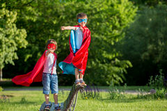 Two sweet little preschool children, boys, playing superhero in. The park, summertime stock photography