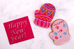 Two sweet mittens with a card. Colored gingerbread on light background. Sweet Christmas gift royalty free stock image