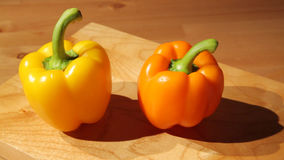 Two sweet peppers on a board. Sliding view of two sweet peppers on a cutting board stock footage