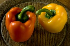 Two sweet peppers on a wooden board. Royalty Free Stock Photos