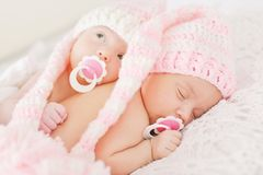Two sweet twins. Are laying on the bed royalty free stock photos