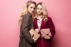 Two sweet young women posing in nice clothes, coat, handbag. Sisters, twins. Spring fashion photo. stock images