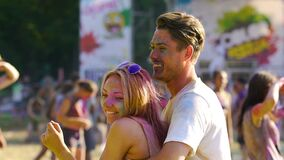 Two sweethearts dancing in a crowd at summer traditional festival of colors. Stock footage stock video footage