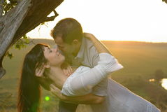 Two sweethearts kissing under tree at sunset Stock Images