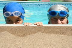 Two Swimmers. Two sisters peek over the edge of the swimming pool after a swimming race Royalty Free Stock Photos