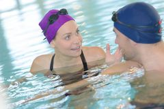 Two swimmers talking in pool. Swimmer Royalty Free Stock Photography