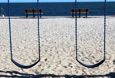 Two swings two benches. Two swings in sandy playground overlooking the ocean view Royalty Free Stock Images