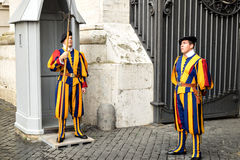 Two swiss guards in traditional uniform on duty at a vatican gate. Yellow, orange,red and blue uniforms of the Pontifical Swiss Guard of the Holy See. Guard post stock photos