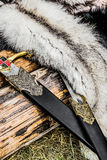 Two swords and some furs over the old log Royalty Free Stock Images