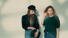 Two Stylish Girls. Two sylish young women posing before white wall, indoor slowmotion stock video