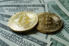 Two symbolic coins of bitcoin on banknotes of one hundred dollar Royalty Free Stock Image
