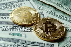 Two symbolic coins of bitcoin on banknotes of one hundred dollar Royalty Free Stock Photo