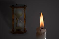 Two symbols. A symbolic image of a candle and a hourglass meaning transience of time and purpose(hope) of life Stock Images